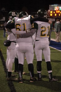 Jervonte Morgan (left) and Kyaire Chambers (right) hold up injured player Kevin Hickman.