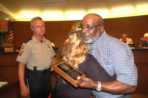 "Angie Wright embraces Wayne ""Skipper"" Braxton in August after he received a plaque commending his heroism for saving her life in Buckingham County in January. Sheriff William G. ""Billy"" Kidd Jr., left, looks on.  Jordan Miles - Herald"