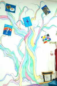 A whimsical tree on Red Door 104's wall holds artwork created by local children.