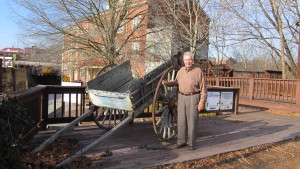 Dr. Jim Jordan examines a one-horse cart that 150 years ago would have rumbled over the streets of Farmville bringing grain to Prince Edward Mills in the background.