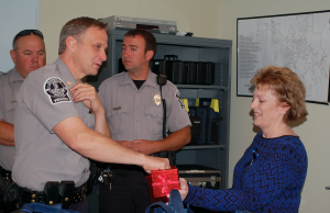 JORDAN MILES | HERALD Janet Bowles holds a box while Police Chief Curtis Davis draws a name for a prize. Jay Talbott, back left, and Eric Ellington look on.