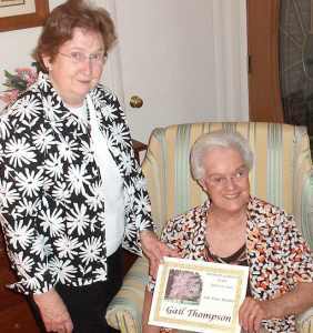 Geraldine Sanderson presents Gail Thompson, seated, with the 2016 Member of the Year Award.