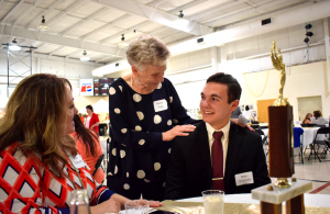 MARGE SWAYNE   HERALD Nancy Haga, center, congratulates Max Gebauer, Fuqua debater who competed in the national Catholic League Tournament this year. At left is Max's mother, Paula Parkhurst.