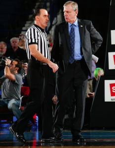 Dr. Ron Bradley, right, confers with a referee during his five years spent as an associate head basketball coach at DePaul University. (Photo by DePaul University)