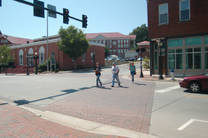 MARTIN L. CAHN | HERALD TOURING — Leanne Sims, left, her father, Edward; and Ukranian exchange student Valeriya Petrechkiv, right, cross Main Street at High Street. Edward Sims said they are hosting Valeriya for the year and were using Labor Day to take her on a tour of Farmville.