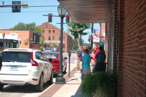 MARTIN L. CAHN | HERALD SHOPPING — A group of people talk outside of one of Main Street's many shops on Labor Day.