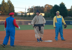 MARTIN L. CAHN | HERALD Super Mario (Assistant Coach Chad Oxendine), left, speaks to Sumo Wrestler (senior infielder Brandon Harvell), who just made it to third base as a Minion (junior right hand pitcher Tyler Wirsu) guards the position.