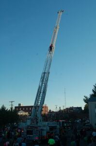 MARTIN L. CAHN | HERALD A firefighter climbs back down a Prince Edward County fire department ladder truck's ladder reaching high into the Friday afternoon sky from the Farmer's Market parking lot during New Life Church's Fall Fest.