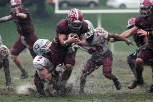HAMPDEN-SYDNEY ATHLETICS Hampden-Sydney College junior running back Mike DeMasi splashes through muddy Fulton Field while running the ball against Guilford College on Oct. 8.