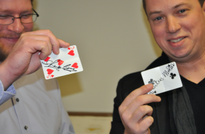 JORDAN MILES | HERALD Crews, right, holds up a card that Herald Sports Editor Titus Mohler, left, placed in his mouth. Crews switched the cards, though both Mohler and Crews held their respectively signed cards in their mouths.