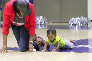 Angelica Tandy tries to coax her son, Joel Saunders, to crawl after taking off his socks to allow him to have more traction.