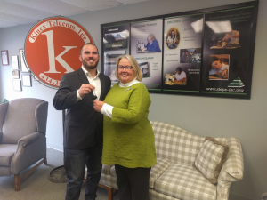 STEPS Inc. President/CEO Sharon Harrup smiles as she receives the keys to a utility truck from Kinex Telecom Project Manager Andrew Lonadier.