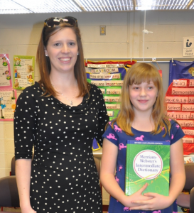 Emily Eroh, winner of the Cumberland Spelling Bee, is presented with her new dictionary by Caroline Vick, Cumberland Middle School media specialist.