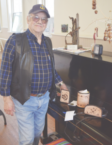 Ramon Stafford stands next to three leatherworking pieces he brought with him to the exhibit.